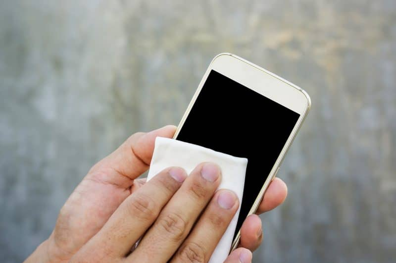 Man cleaning his smartphone with a microfiber cloth - Celside Magazine